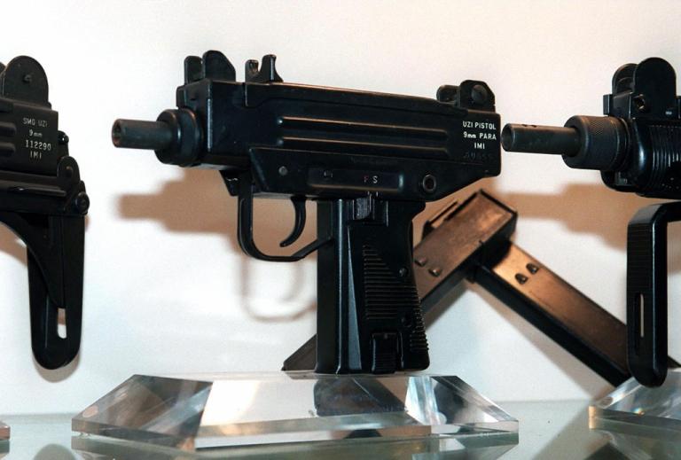 <p>An Uzi pistol (C) is displayed next to the larger Uzi submachine gun models, at the Israeli Military Industries (IMI) in Ramat Hasharon 11 November, 1997.</p>