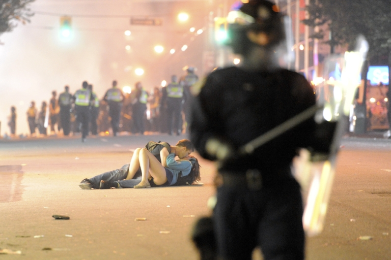 <p>Riot police walk in the street as a couple kiss on June 15, 2011 in Vancouver, Canada. Vancouver broke out in riots after their hockey team the Vancouver Canucks lost in Game Seven of the Stanley Cup Finals. This
