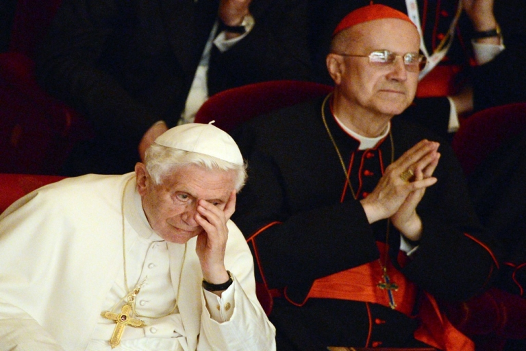 <p>Vatican State Secretary Cardinal Tarcisio Bertone (R) and Pope Benedict XVI at La Scala theater Orchestra during a concert in Milan on June 1, 2012. Bertone is quickly becoming the target of a recent scandal involving leaked Vatican documents.</p>