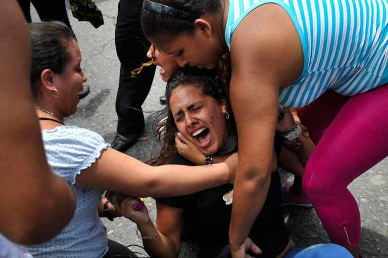 <p>Relatives of inmates of El Rodeo I and II penitentiaries cry outside the prisons compounds in Guatire, outskirts of Caracas.</p>