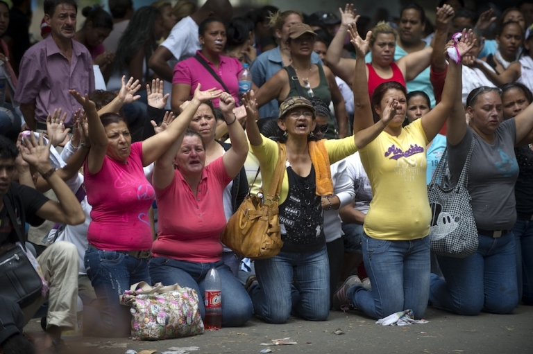<p>Relatives of inmates kneel during a demonstration after a riot in front of La Planta prison in Caracas on April 30, 2012. The authorities of the Ministry of Correctional Services are trying to negotiate voluntary transfers to other prisons.</p>