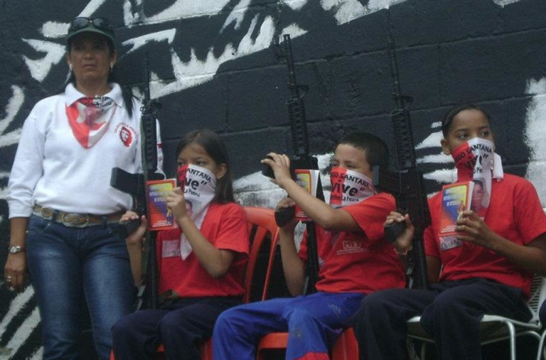<p>Children with weapons in one of Caracas' slums</p>
