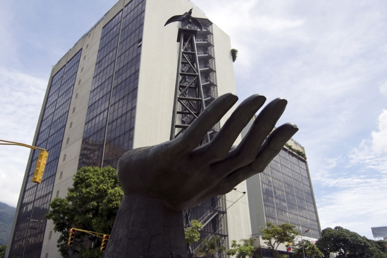 <p>A statue of a hand with an oil drilling rig out front of Venezuela's state oil company PDVSA.</p>