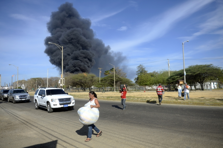 <p>Local residents evacuate the surroundings of Venezuela's Amuay oil refinery, which burst into flames early Saturday, killing more than 40 people in one of the worst world's refinery blasts in decades.</p>