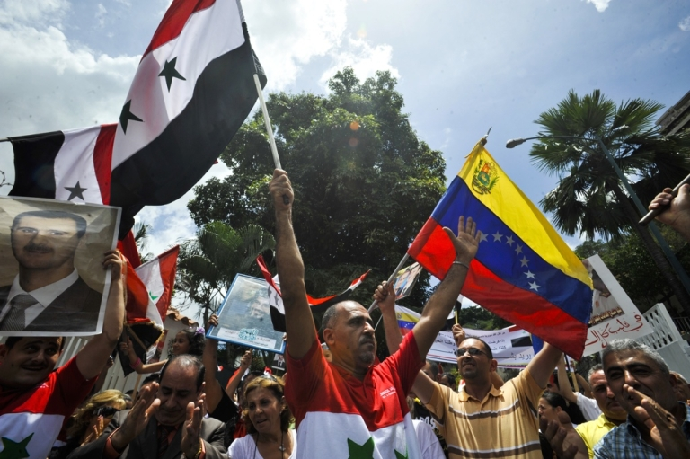 <p>Demonstrators wave Syrian and Venezuelan flags and hold a picture of Syrian President Bashar al-Assad in front of the Syrian Embassy in Caracas, Venezuela on April 1, 2011.</p>