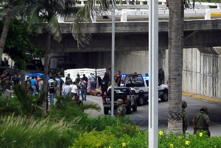 <p>Officials swarm the scene in Veracruz, where 35 bodies were dumped in the street.</p>