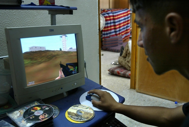 <p>Tarek Owweis plays a videogame call 'Jenin street of Heros' in Jenin in the West Bank 22 September 2004. The fiercest fighting of the entire intifada took place in Jenin in April 2002 when 23 Israeli soldiers and around 50 Palestinians were killed in a vast army raid, dubbed Operation Defensive Shield. Ever since, Jenin and its refugee camp, comprising 70,000 inhabitants, have been seen as the ultimate symbols of the Palestinian struggle against Israeli occupation.</p>