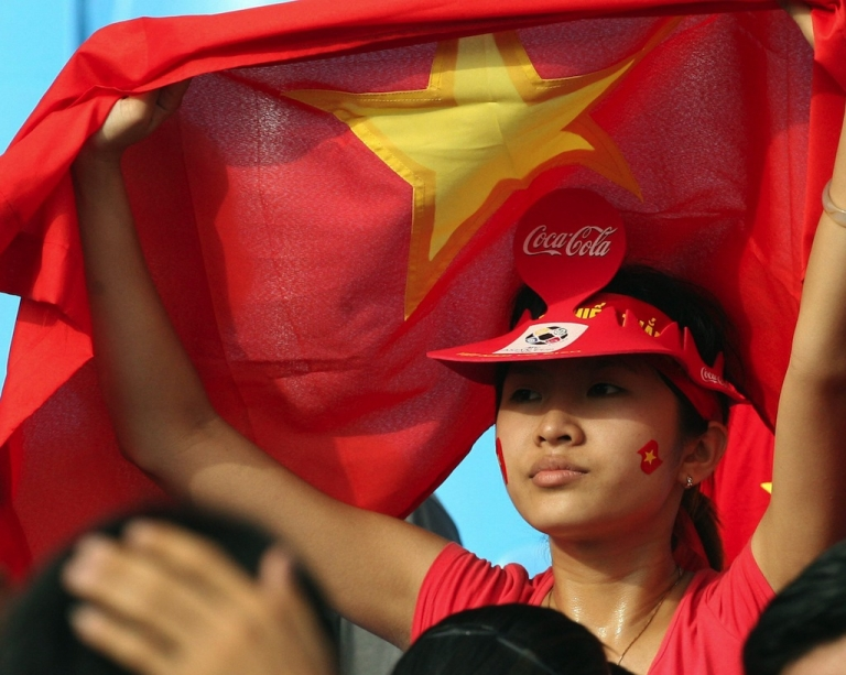 <p>A young Vietnamese girl shields herself with a national flag at a Hanoi stadium.</p>