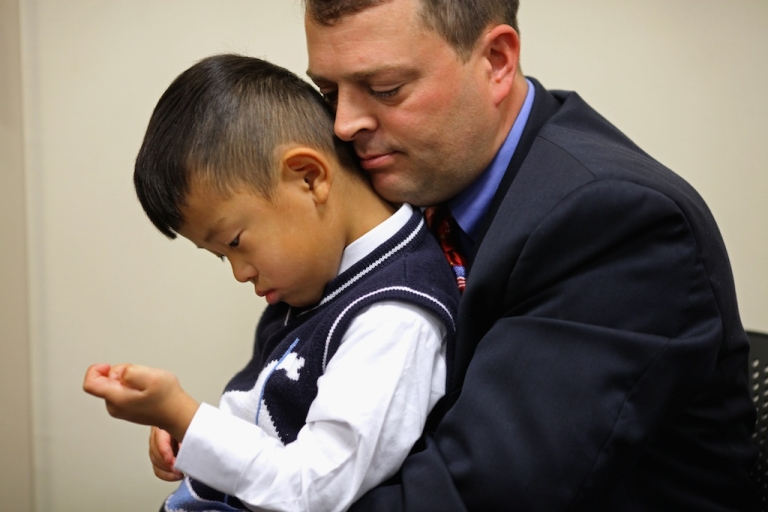 <p>Noah Avery, 4, is held by his adopted father Alex Avery of Stanton, Virginia, during the children's citizenship ceremony at the U.S. Citizenship and Immigration Services office November 14, 2011 in Fairfax, Virginia. Twenty-five children from nine countries, including Bulgaria, China, Ethiopia, Guatemala, Korea, Liberia, Russia, Taiwan and Vietnam, celebrated their U.S. citizenship during the ceremony.</p>