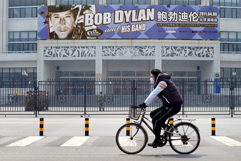 <p>A cyclist rides by the venue in Beijing where U.S. music legend Bob Dylan played his first concert in China on April 6, 2011.</p>