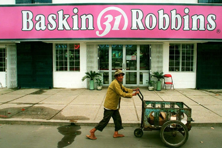 <p>An elderly man pushes his cart past a newly opened Baskin-Robbins ice-cream shop in Ho Chi Minh City, Oct. 21, 1995.</p>