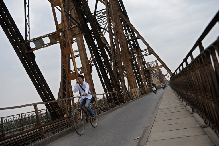 <p>A Vietnamese man talks on his mobile phone as he rides his bicycle on an old colonial-era iron bridge on the outskirts of Hanoi on Oct. 27, 2010.</p>