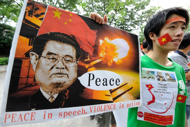 <p>A Vietnamese youth holds up a placard during a rally denouncing China over the recent rise in tensions over territorial claims in the South China Sea on June 25, 2011.</p>
