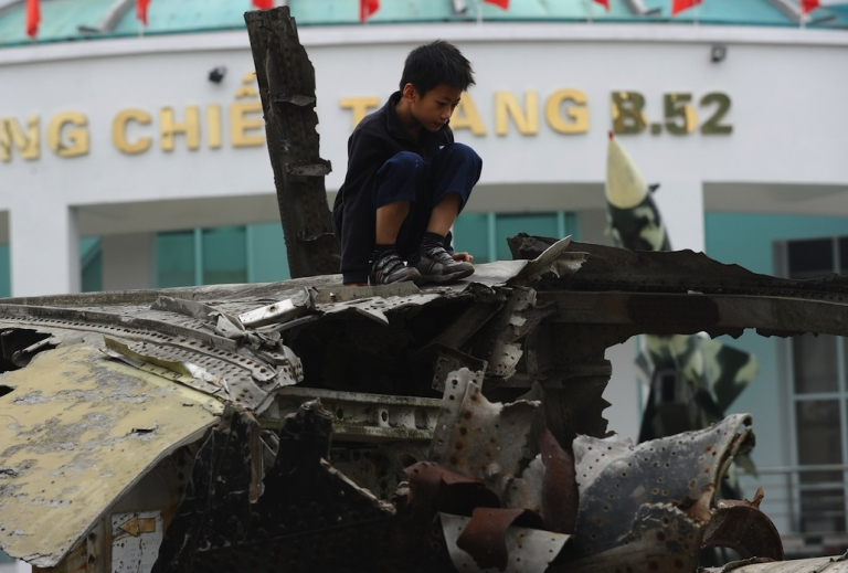 <p>A boy sits on top of wreckage of a downed US Air Force B-52 aircraft on display in Hanoi, Vietnam, on December 19, 2012.</p>