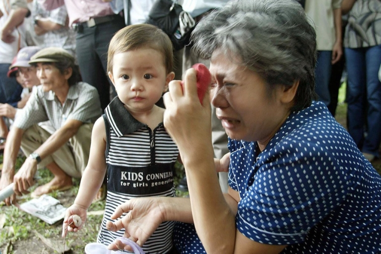 <p>Nguyen Thi Ha, aunt of Ho Thanh Tung, one of six defendants sentenced to death, sits crying next to her grand-son outside Ho Chi Minh-City's Court where the judge announced the sentences of the country's biggest ever corruption scandal, June 5, 2003.</p>