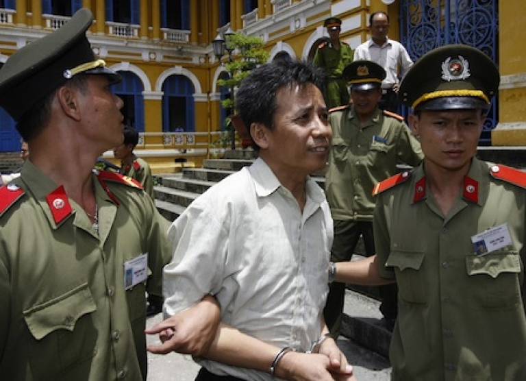 <p>Vietnamese political dissident Le Nguyen Sang is led out a Ho Chi Minh City court after being sentenced to a five-year jail term in 2007.</p>