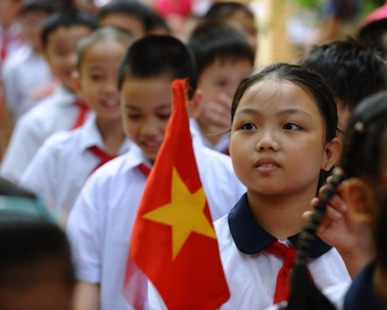 <p>A student holds a flag during a ceremony marking the new school year at a local elementary school in downtown Hanoi on September 5, 2012.</p>