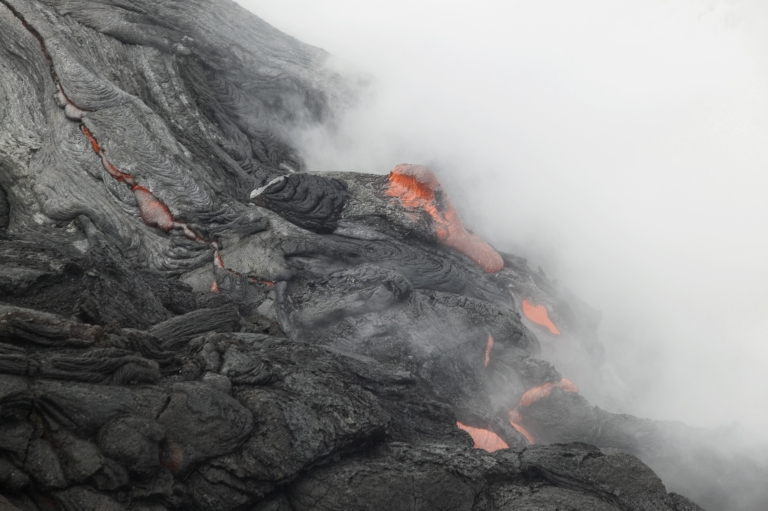 <p>Lava flows into the ocean from Kilauea Volcano at Volcanoes National Park in Hawaii on June 6, 2004.</p>
