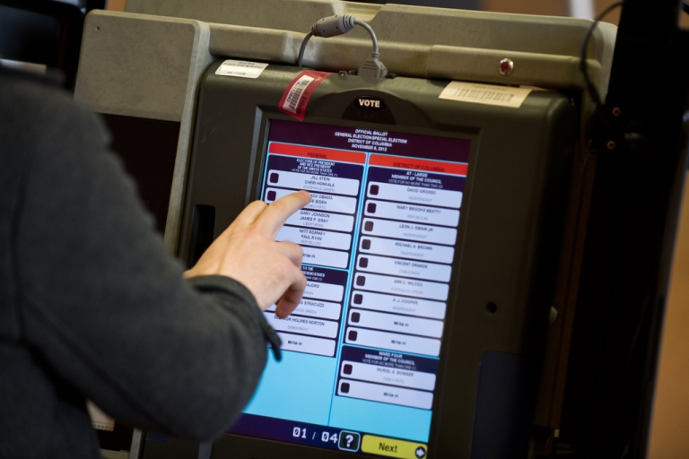 <p>A man casts his electronic ballot at a polling station in Washington, DC on November 6, 2012.</p>