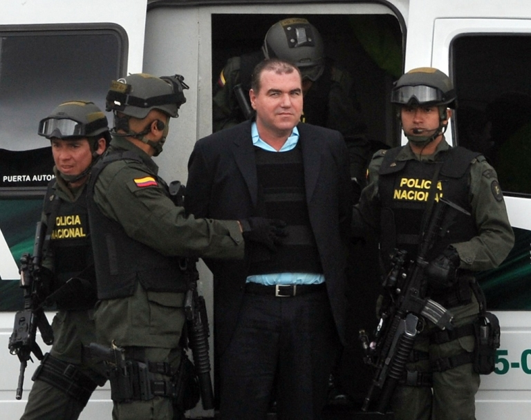 <p>Colombian police officers escort Venezuelan drug trafficker Walid Makled to an aircraft to be extradited to Venezuela on May 9, 2011 at the anti-narcotics air base in Bogota. Makled, arrested in August 2010 in Colombia, was also requested in extradition by the United States, where he is accused of drug trafficking, but the Colombian government argued that Caracas had made the request first and that the crimes for which he is wanted in his country, including murder, are more serious.</p>