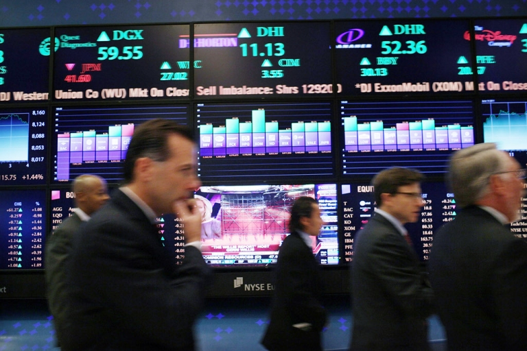 <p>Traders work on the floor of the New York Stock Exchange in New York City. Investors erased early gains today amid concerns the Spanish bailout deal will increase the country's already heavy debt burden.</p>