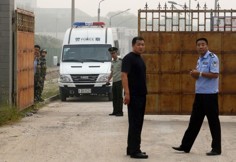 <p>Chinese police wait outside the Beijing No. 2 prison after the release of dissident Wang Xiaoning on August 31, 2012.</p>