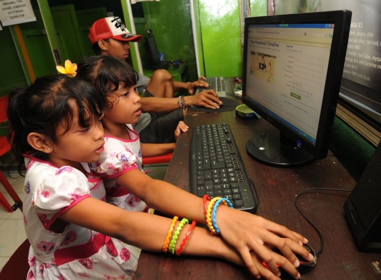 <p>In this photograph taken February 2, 2012, Indonesian children log onto a Facebook page at an internet shop on the resort island of Bali.</p>