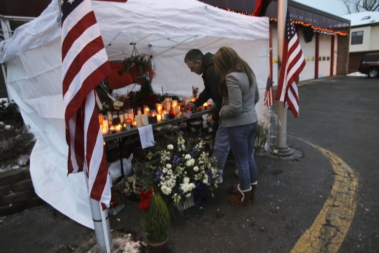 <p>Mourners place an American flag at a makeshift memorial at the West Webster Fire Station on December 26.</p>