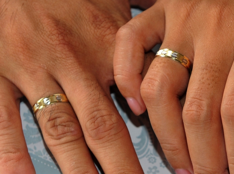 <p>A couple holds hands showing their wedding rings.</p>