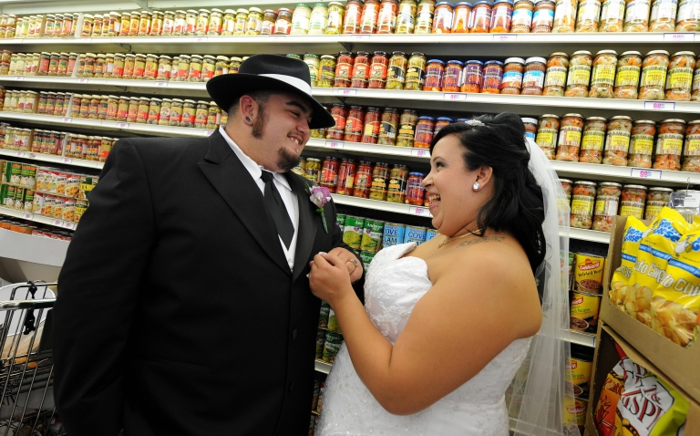 <p>Lesley Barragan and John Tinker smile as they look at the rings after their 99 cent wedding ceremony at the 99 cent store in Los Angeles on September 9, 2009.</p>