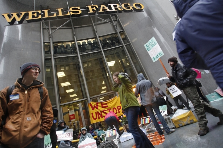 <p>Occupy San Francisco protesters march outside a Wells Fargo branch in San Francisco's financial district to protest against major banks in January.</p>