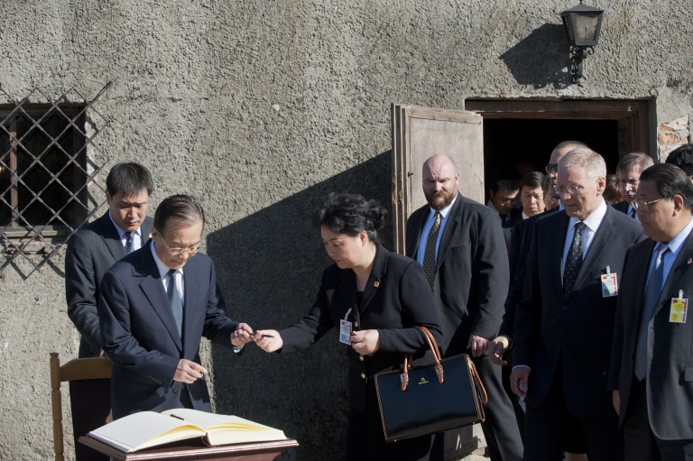 <p>Prime Minister Wen signs a visitor's log book today after his visit to the Museum of Auschwitz in Oswiecim, southern Poland.</p>