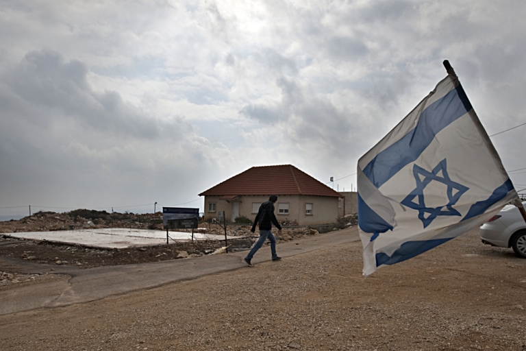 <p>An Israeli flag flies in the wind as a Jewish settler walks past the remaining foundations of a demolished house, in the unauthorized West Bank settlement of Migron. Settlers have agreed to leave the oldest and largest settlement in the West Bank, as part of a deal with the Israeli government on March 11, 2012.</p>