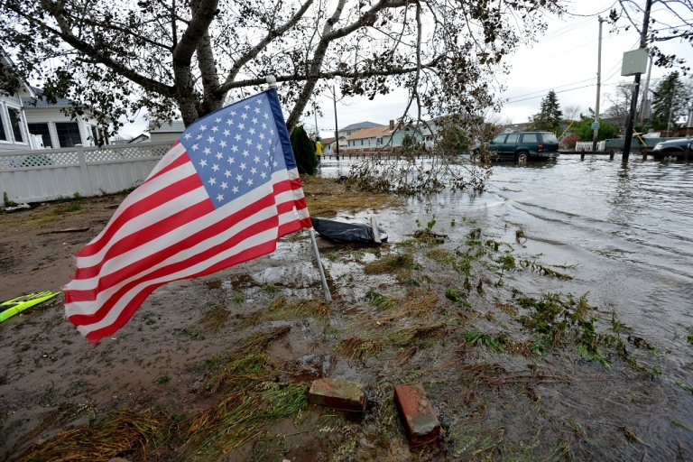 <p>An American flag flies from the front yard of a house in a flood damaged area October 30, 2012 in the Breezy Point area of Queens in New York that was hit hard by Hurricane Sandy.</p>