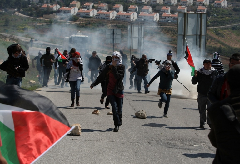 <p>Palestinian protestors run away from tear gas fired by Israeli soldiers during clashes between Israeli soldiers and a group of Palestinian and foreign demonstrators in the West Bank village of Nabi Saleh, near Ramallah on March 23, 2012, following a protest against Palestinian land confiscation to build a Jewish settlement Hallamish nearby.</p>