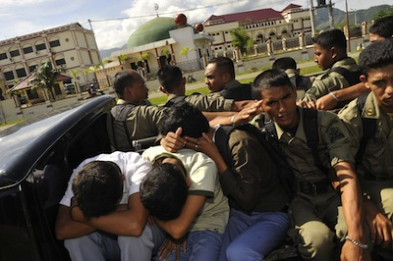 <p>This photo taken on December 4, 2009 shows three Acehnese youths (L) being arrested by a team of Sharia police in Banda Aceh after they were caught gambling over dominoes at a cafe across from a mosque. Most Muslims in the country of 234 million people are modern and moderate, and Indonesia's constitution recognises five official religions including Buddhism and Christianity. But Aceh has special autonomy, and one of the ways it has defined itself as different from the rest of the country is through the implementation of sharia law and the advent of the religious police.</p>
