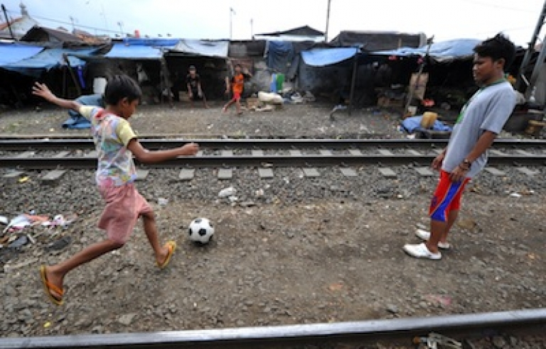 <p>Indonesian boys practice football skills in the space between railway tracks in Jakarta on February 16, 2011.</p>