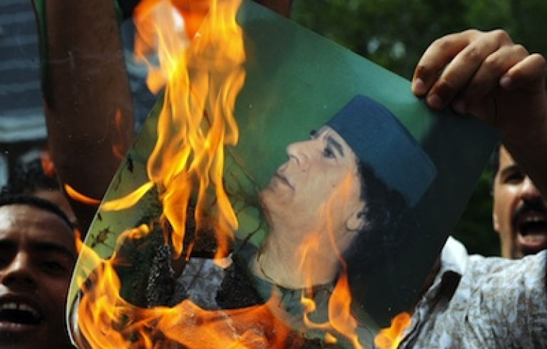 <p>A Libyan protester burns a portrait of Libyan leader Moamer Kadhafi in front of the Libyan embassy in Kuala Lumpur, Malaysia, on February 23, 2011.</p>