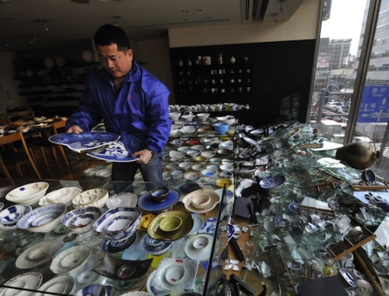 <p>The owner of a ceramic shop checks his damaged wares following the massive 8.9-magnitude earthquake in Tokyo on March 11, 2011. The huge earthquake shook Japan, unleashing a powerful tsunami that sent ships crashing into the shore and carried cars through the streets of coastal towns.</p>