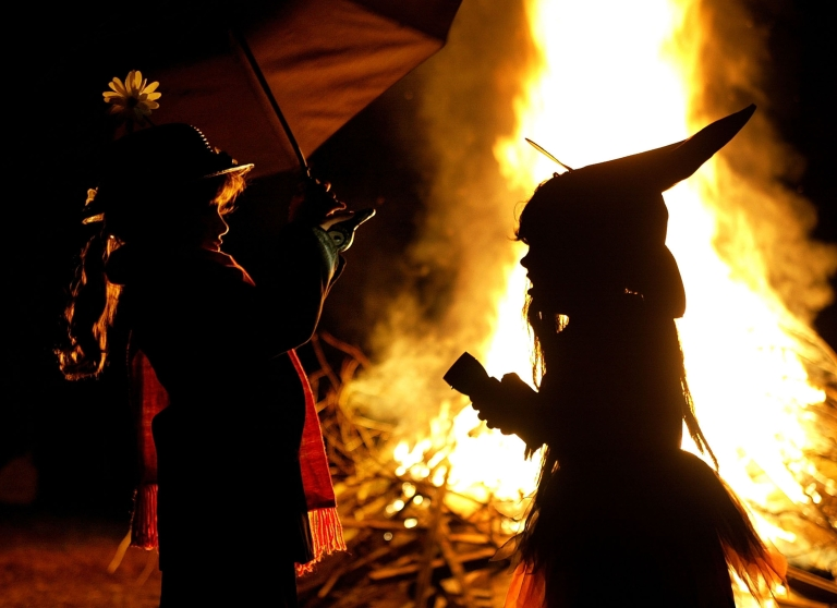 <p>Dressed as a witch, Leigh Kosega (R) and Zabell Carstens dressed as Mary Poppins stand near a bon fire October 25, 2003 in Huntingtown, Maryland.</p>
