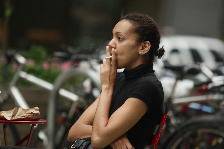 <p>A woman smokes a cigarette in the pedestrian thoroughfare located in Times Square May 23, 2011 in New York City. A new study has found that quitting smoking by 30 almost eliminates early death risk.</p>