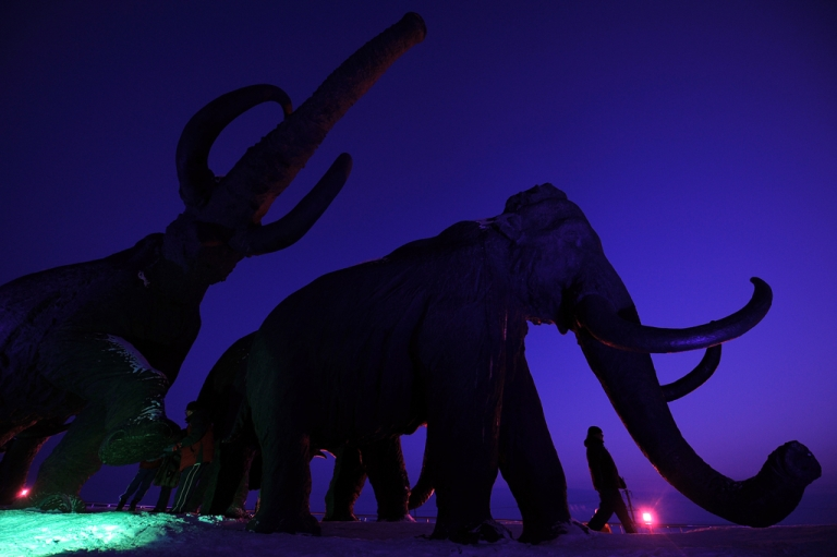 <p>A person walks past giant bronze sculptures of mammoths on March 7,  2011 during the World Biathlon Championships in the Siberian city of Khanty-Mansiysk.</p>