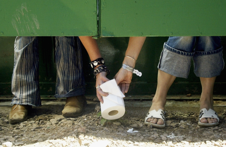 <p>Two festival-goers pass a roll of toilet paper between toilet cubicles, during the 2004 Glastonbury Festival at Worthy Farm, Pilton, Somerset, England.  June 25, 2004.</p>