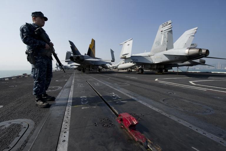 <p>A US Navy serviceman holding a machine gun stands near F/A-18 Hornet warplanes on the flight deck of the USS Carl Vinson,</p>