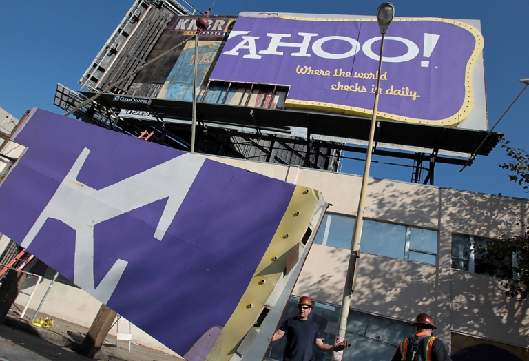 <p>A worker moves a section of a Yahoo! billboard onto a truck in San Francisco, California. The company has seen its first resignation in the wake of the scandal over CEO Scott Thompson's botched academic record: board director Patti Hart.</p>