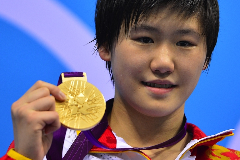 <p>Chinese swimmer Ye Shiwen poses on the podium with her gold medal after winning the women's 200-meter individual medley final at the London Olympics on July 31, 2012.</p>