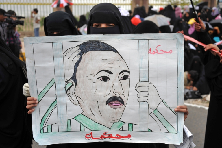<p>A Yemeni anti-government protester holds a drawing calling for the trial of President Ali Abdullah Saleh.</p>