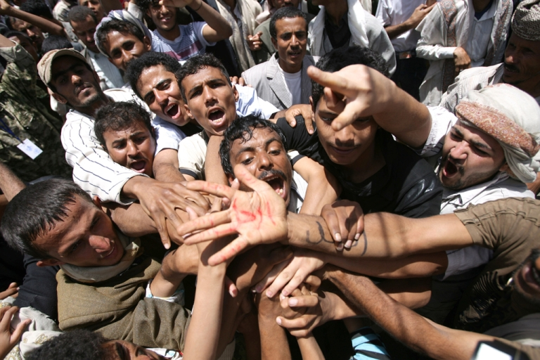 <p>Yemeni protesters shout slogans and show a palm with writing in Arabic that reads,