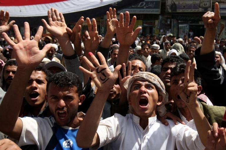 <p>Tens of thousands of anti-government Yemeni mourners chant slogans as they gather next to the bodies of activists who were among more than 50 protesters gunned down by snipers in Sanaa on March 20, 2011 during a mass funeral procession in the capital.</p>
