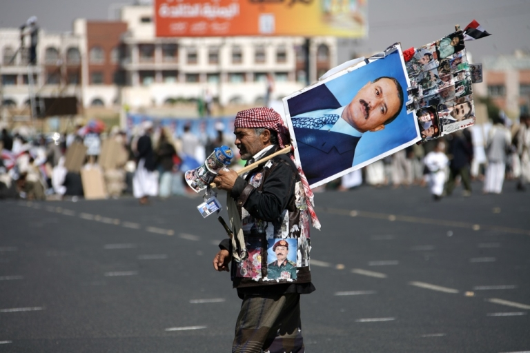<p>A Yemeni supporter of President Ali Abdullah Saleh wears and carries portraits of the embattled leader during a pro-regime rally on Dec. 2, 2011.</p>